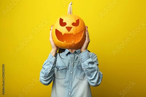Papiers peints Pays d Afrique Female hands holding halloween pumpkin on yellow background