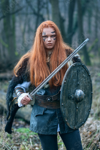 Fotografie, Obraz  Portrait of beautiful redhead northern warrior woman with with sword, shield in