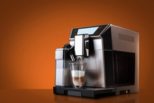 Coffee Machine Without Flying Coffee Beans Across It On Orange Background. Concept Studio Shooting. High Speed Freezing Photo