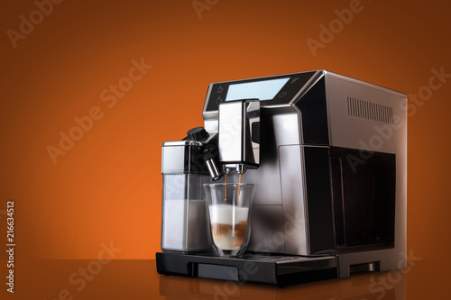 Fotografiet Coffee machine without flying coffee beans across it on orange background