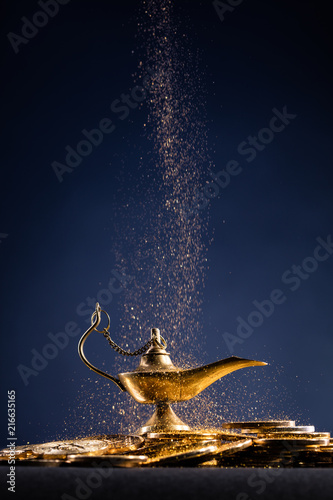 Magic lamp of wishes on stacks of gold coins with golden dust Wallpaper Mural