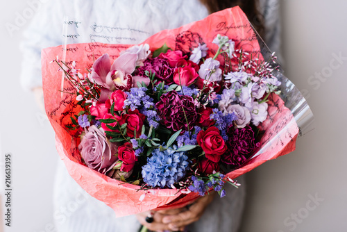 Very Nice Florist Woman Holding A Big Beautiful Fresh Flower Bouquet Of Carnations Roses Hyacinths Mattiola Orchids In Lavender And Crimson Colors On The Grey Wall Background Close Up View Buy