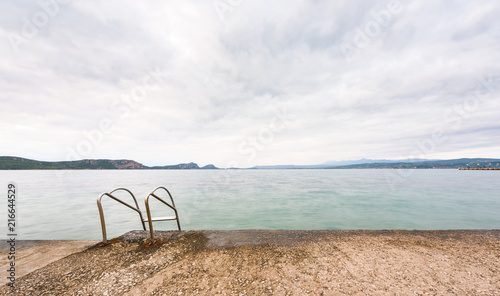Overcast seascape from a jetty with swimming pool ladder plungeing in to the sea in Pylos, Greece.