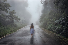 Back View Of Young Woman Walking On The Road Surrounded Dense Fog And Silhouette Of Tree In Winter.