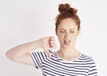 Woman Showing Thumb Down And Grimacing At Studio Shot