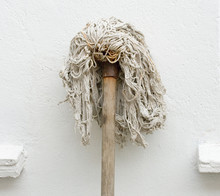 Mop Resting Against A White Wall