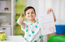 Childhood, Education And People Concept - Happy Smiling Boy Holding School Test With A Grade Showing Thumbs Up
