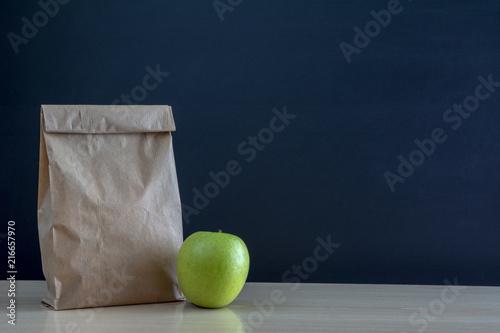 Fotografía  Bolsa de almuerzo de papel en el  pupitre de la escuela con una manzana verde