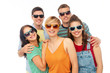friendship, summer and people concept - group of happy smiling friends in sunglasses hugging over white background