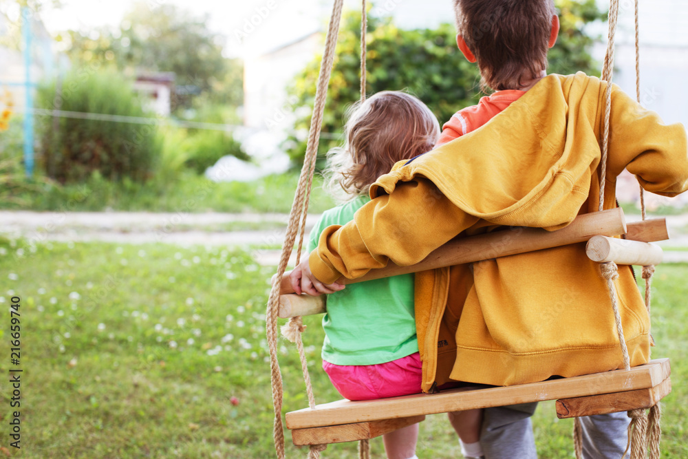 Fototapety, obrazy: children sitting on a swing in the garden. older brother hugging little sister