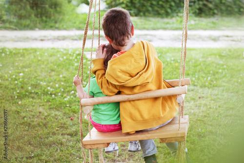 children sitting on a swing in the garden Fototapeta