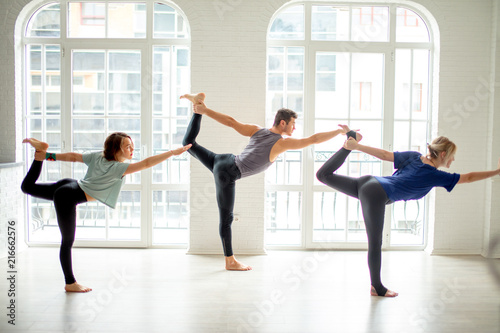 Unity Of Mind And Body People Practicing Pilates Or Yoga Three Professional Sportspeople Performing The Most Beautiful And Difficult Yoga Or Pilates Pose Against Bright Day Light Big Windows Buy