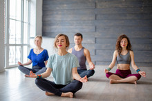 Young Office Workers People Relaxing Their Body And Free Their Minds From Thoughts At Yoga Classes Indoors, Sitting In Lotus Position With Closed Eyes, Keeping Fingers In Mudra Gesture