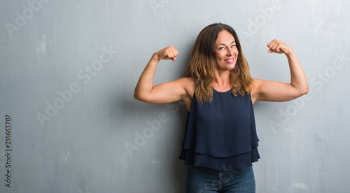 Middle age hispanic woman standing over grey grunge wall showing arms muscles smiling proud. Fitness concept.