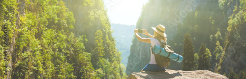 Girl hipster traveler takes pictures of nature on the background of mountains Tourist traveler on background valley landscape view mockup