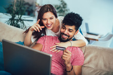 Man Using Laptop And Woman Holding Credit Card. Young Couple Shopping Online With Credit Card At Home