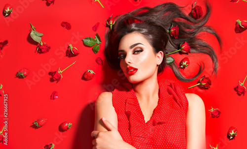Poster - Beauty sexy model girl lying on red background with rose flowers and strawberries. Beautiful brunette young woman with long hair and perfect make-up, red seductive lips, smoky eyes. Trendy makeup