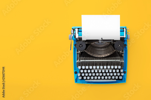 Foto Typewriter machine in retro style on yellow background. Top view.