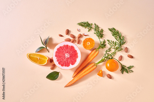 Carrot, slices of orange and grapefruit, mandarins, almonds, green leaf on a paper background. Concept of colorful organic food.