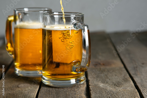 Spoed Foto op Canvas Bier / Cider Pouring beer in glasses on rustic background