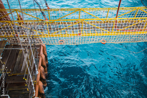 View of an offshore crew walking at the gangway to offshore drilling rig with life life buoys