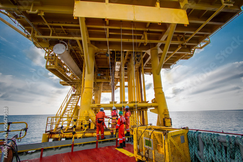 Fotografia Supply boat or crew boat transfer cargo to oil and gas industry and moving cargo from the boat to the platform, boat waiting transfer cargo and passenger between oil and gas platform