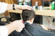 Barber Giving Haircut To Client Using Trimmer In Shop