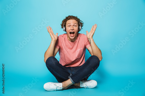 Fotobehang School de yoga Portrait of an excited young curly haired man