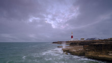 Summer Sunrise With Stormy Clouds And Slow Shutter Speed At Portland Bill Light, Dorset, UK