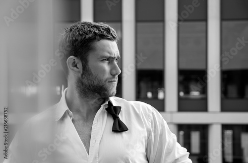 Fotografía  Handsome hunky man with unbuttoned shirt and loose bowtie stands on hotel balcon