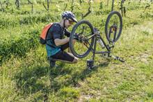 Young Man Repairing Mountain Bike On Field