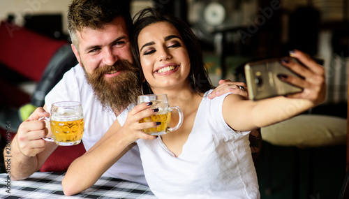 Leinwand Poster Couple in love on date drinks beer