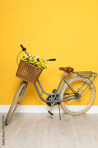 Fotobehang Fiets Retro bicycle with wicker basket near color wall