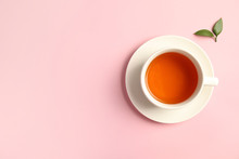 Cup Of Delicious Tea With Green Leaves On Color Background, Top View