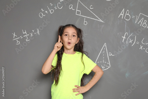 Little school child and mathematical formulas on grey background
