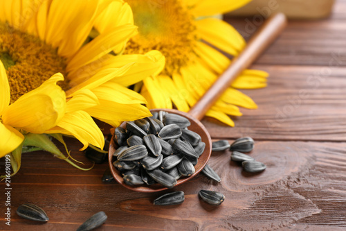 Spoon with sunflower seeds on wooden table, closeup