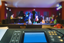 Unrecognizable Musician. View Of A Blurred Stage And Focus On A Modern Digital Sound Mixer. Subjective View Of The Sound Engineer