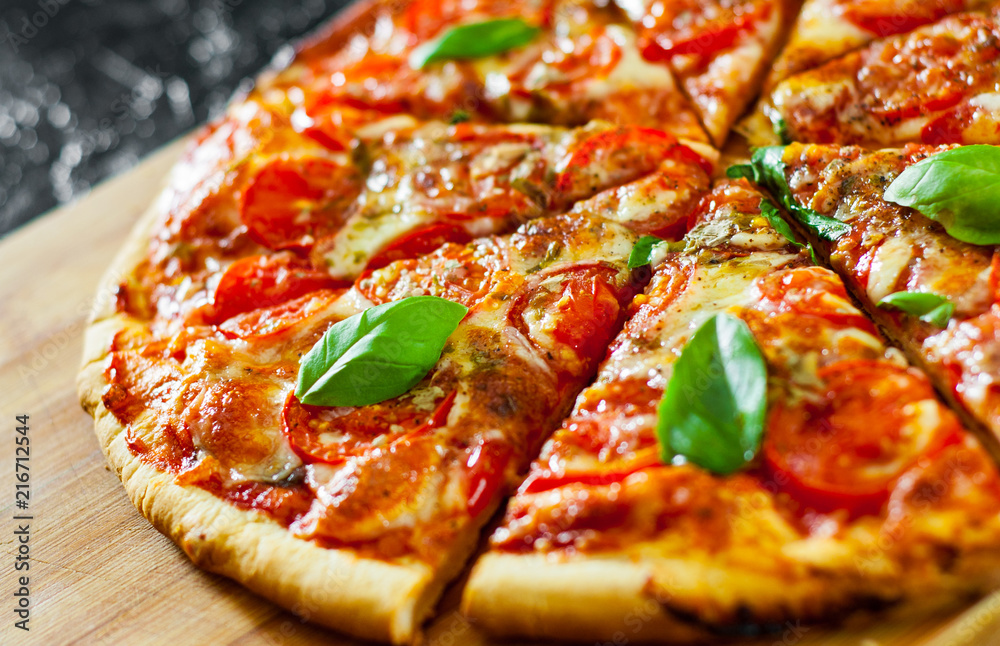 Fototapety, obrazy: sliced Pizza with Mozzarella cheese, Tomatoes, pepper, Spices and Fresh Basil. Italian pizza. Pizza Margherita or Margarita