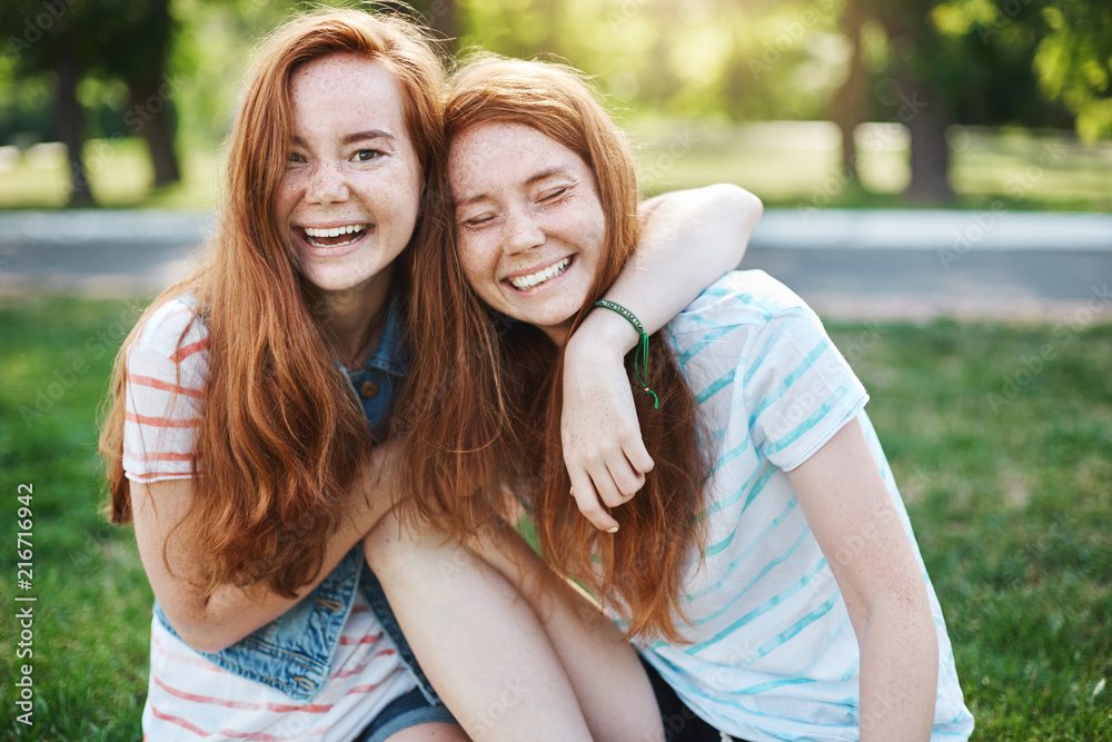 Fototapety, obrazy: Wanna hug her forever. Portrait of happy and carefree two twin sisters with natural red hair and freckles, laughing out loud and cuddling, fooling around while resting in park on fresh green grass
