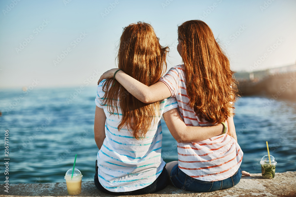 Fototapety, obrazy: Girs making promises never leave each other, gazing at beautiful sea and hugging, sitting near docks, dreaming about future, talking casually like sisters and enjoying warm sunny evening together
