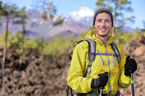 Hiker man hiking in forest mountain background. Happy healthy young fit sport person with backpack, jacket and hat trekking in nature during spring outdoors. Mountains landscape.
