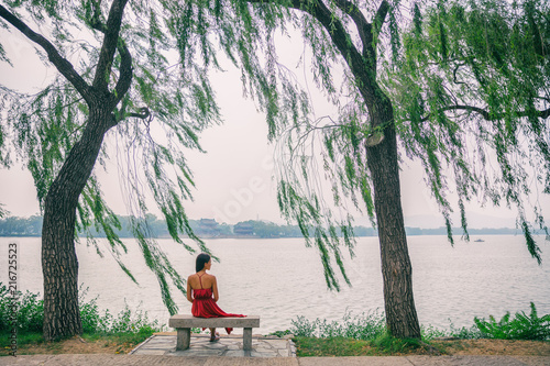 Keuken foto achterwand Aziatische Plekken Nature lake woman sitting on park bench relaxing at view of Summer Palace in Beijing, China. Asia travel. Romantic scenery of lady in red dress under weeping willow trees in serenity.