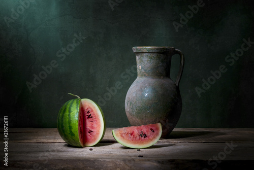 still life with one small whole green watermelon, two peers, a jug and a bunch of ears and poppy seed heads. Art photography.