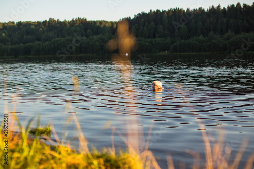 Valokuva  Elderly woman swimming in the river at sunset.