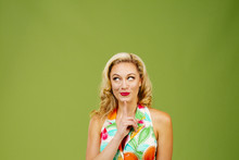 Wishing For....Portrait Of A Beautiful Blonde Woman With Finger Un Chin, Isolated On Green Studio Background