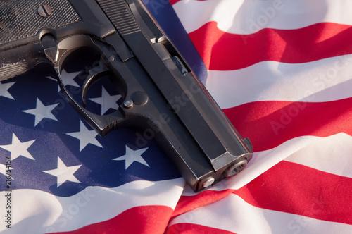 Fotografia, Obraz  A black pistol shown laying on an American flag