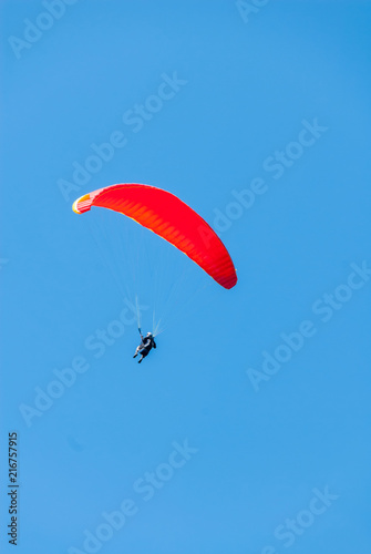 Fotografía  Hang glider soars through a pristine blue sky