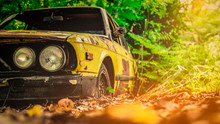 Old Wrecked Car In Vintage Style. Abandoned Rusty Yellow Car In The Forest. Closeup Front View Headlights Of Rusty Wrecked Abandoned Car On Blurred Green Tree Background . Art Of Abandoned Used Car.