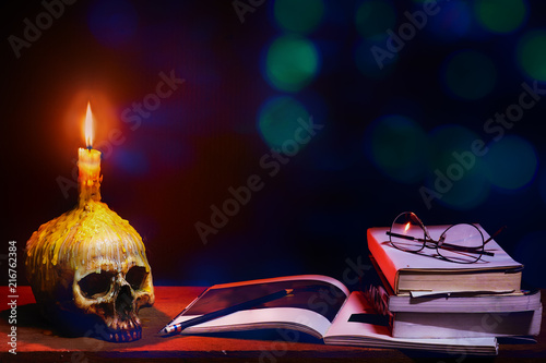 Cuadros en Lienzo Still life image of wizard wooden desk with skull of lighting candle and books w
