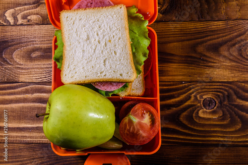Foto op Aluminium Assortiment Lunch box with sandwich, cucumbers, green apple and tomatoes on wooden table. Top view